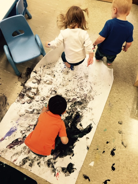 toddlers exploring paint with feet